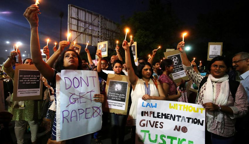 FILE PHOTO: People hold candles and placards during a protest against the rape of an eight-year-old girl, in Kathua, near Jammu, a teenager in Unnao, Uttar Pradesh, and an eleven-year-old girl in Surat, Gujarat, in Ahmedabad